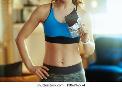 Closeup on young sports woman in sport clothes with chocolate bar in the modern house.