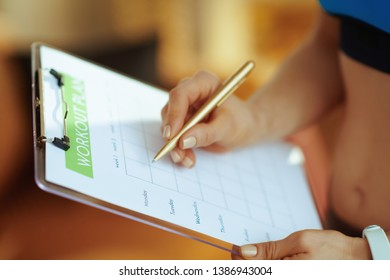 Closeup on young sports woman in fitness clothes in the modern house filling meal plan.