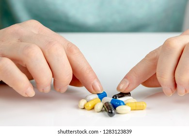 Closeup on young woman choosing colorful pills