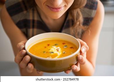 Closeup on young woman enjoying pumpkin soup