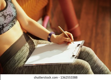 Closeup on young woman in fitness clothes with clipboard and pen writing training log in the modern house.