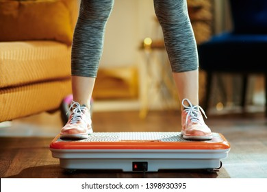 Closeup on young woman in fitness clothes in the modern house training using vibration power plate.