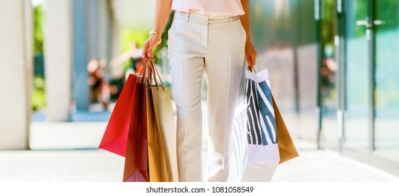 Closeup on young woman with shopping bags on the mall alley