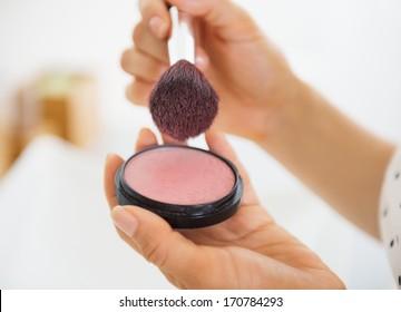Closeup on young woman using blush