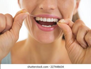 Closeup on young woman using dental floss