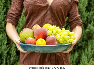 Closeup on a young woman's hand as she is standing in her garden. Girl holding a basket of fruits apples lemons grapes peaches and mango at summer green park fresh and  healthy sexy lifestyle