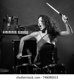 Closeup of one beautiful emotional expressive cool young brunette sexual rock musician woman with long curly hair standing in recording studio playing drums with sticks near electro guitar