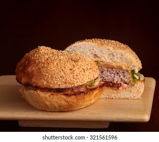Closeup of one big tasty appetizing fresh burger of green lettuce red tomato cheese and bacon slice meat cutlet and white bread bun with sesame seeds cut on two half, horizontal picture