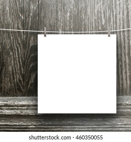 Close-up of one blank square frame hanged by pegs against wooden background