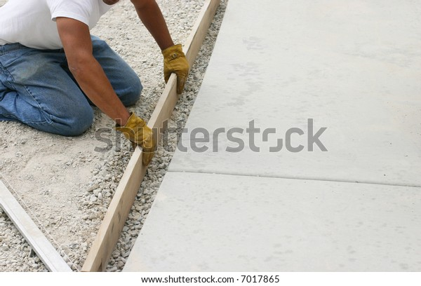 close-up one construction man kneeling holding piece of lumber preparing for concrete