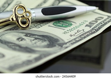 closeup of a one hundred dollar bill, gold key and pen reflecting on black - finance concept