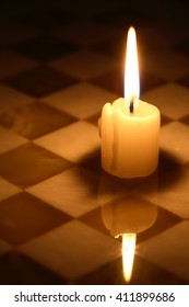 Closeup of one lighting candle on stone chessboard