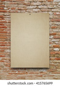 Close-up of one nailed blank brown canvas frame on weathered brick wall background