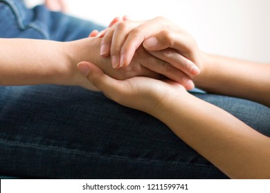 Close-up of one person holding hands for give more hope and spirit to another.