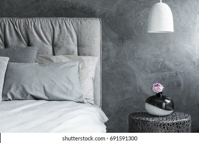 Close-up of one side of gray bed, white pendant lamp and textured wall in the background