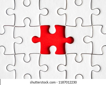 Closeup one white jigsaw puzzle beside missing jigsaw group on red background with top view (Business Concept)