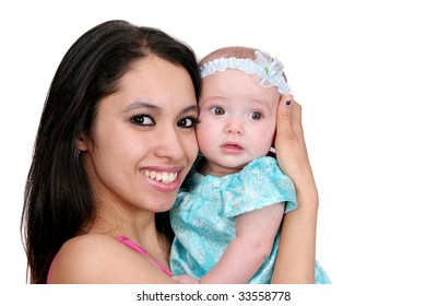 closeup of one young dark haired mother in pink and her young baby girl child