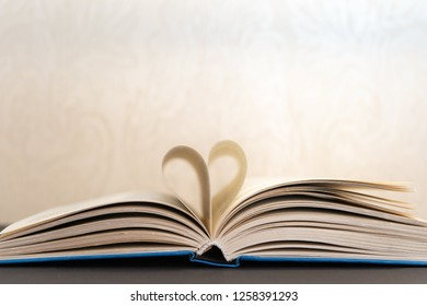 Close-up of an open book with heart shaped pages on white background