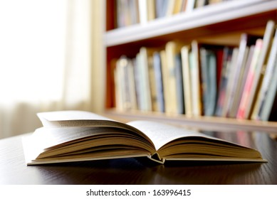 Close-up of an open book , on a wooden table, with bookshelvClose-up of an open book , on a wooden table, with bookshelves in the background, as an invitation to study literaturees in the background,