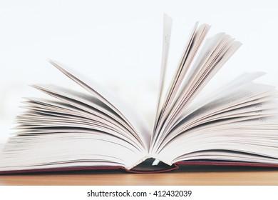 Closeup of open book on wooden desktop