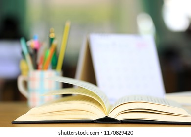 Close-up of open books on the desk stationery and desktop calendar are the background selective focus and shallow depth of field