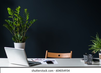 Close-up of open laptop on white table. Nearby is a tablet computer, a smartphone, paper graphics, pencil holder. In the background a dark wall and house plants. Empty workplace.