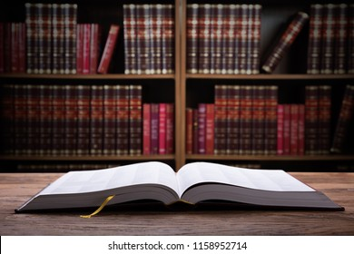 Close-up Of An Open Law Book On Wooden Desk In Courtroom