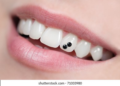 Closeup of open mouth with dental jewelry tooth. Intentional very shallow depth of field.