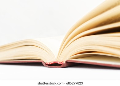 Closeup open old books against a light beige background. Shallow focus. Copyspace.
