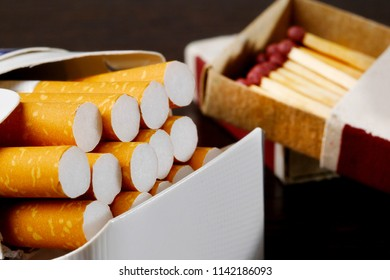 closeup of open pack of cigarettes and box of matches on background