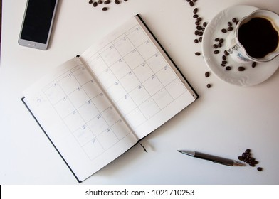 Closeup of opened diary book with coffee, pen and phone. Planner on a table with phone.