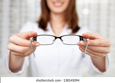 Closeup of optometrist, optician giving glasses  to try