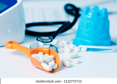 closeup of an orange beach shovel and some pills, on a doctors desk, next to a blue plastic beach pail and a stethoscope, in a doctors office, depicting the medical assistance in summer