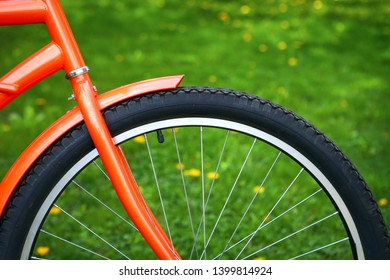 Closeup of orange Bicycle against green grass with dandelions