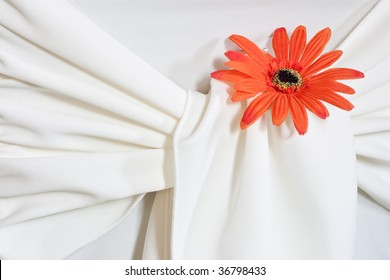 A closeup of an orange daisy designed into the seat covering for a wedding, surrounded by fabric.
