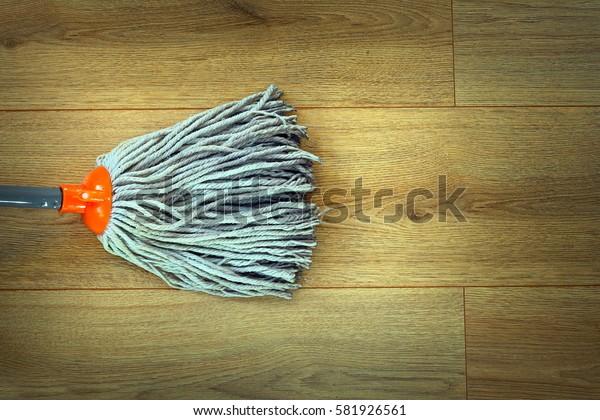 closeup of orange mop head cleaning on beige wooden parquet