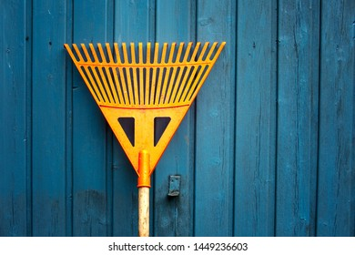 closeup of orange rake leaning at blue wooden wall