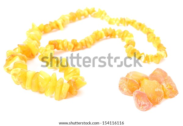 Closeup of orange, shiny amber necklace for the woman and raw amber. Isolated on white background