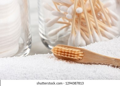 A closeup of an organic biodegradable bamboo toothbrush with bamboo cotton swabs in the blurred background