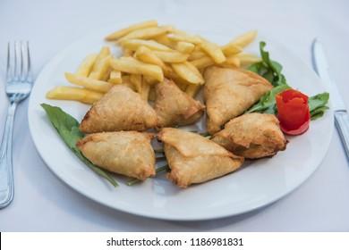 Closeup of oriental sambousek appetizer meal in luxury outdoor restaurant setting