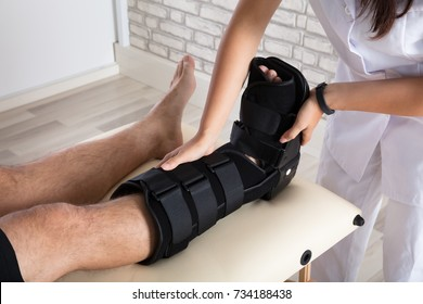 Close-up Of A Orthopedist Putting Walking Brace To Patient's Leg