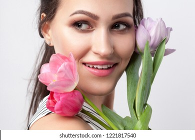 closeup ortrait of young brunette beautiful woman with makeup in striped dress, standing and holding tulips and looking away with toothy smile. indoor studio shot, isolated on light grey background.