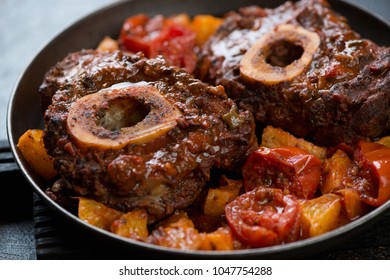 Closeup of osso buco made of cross cut veal shank with oranges and tomatoes, selective focus, studio shot