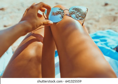 Close-up outdoor photo of sensual tanned female legs with fashionable sunglasses