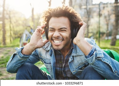 Close-up outdoor portrait of handsome african man with afro haircut holding hands on headphones while listening to music and being excited, sitting in park. Musician gets inspiration