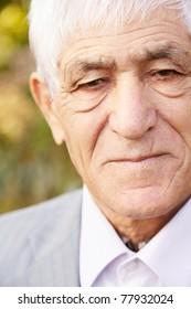 Closeup outdoor portrait of serious caucasian senior man