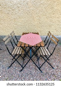 Closeup of outdoor restaurant table and chairs with red and white table cloth, romanticly set up on gravel ground towards a yellow plastered wall with copy space.
