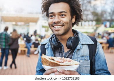 Close-up outdoor shot of happy emotive young dark-skinned male with afro hairstyle, wearing headphones over neck and denim coat, holding sandwich and looking aside while being on city festival
