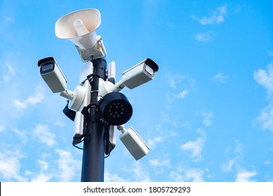 Close-up of outdoor surveillance cameras, floodlights and loudspeakers on a street pole. Ensuring security on the street. Security cameras and speakers on a pole above a blue sky.