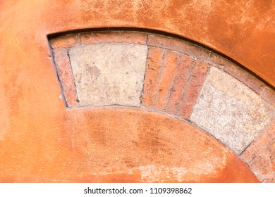 Close-up outdoor view of a decorative ancient stone arch element incorporated in a concrete wall. Frame traces of an ancient window with an arch made of stone blocks. Abstract architectural image.